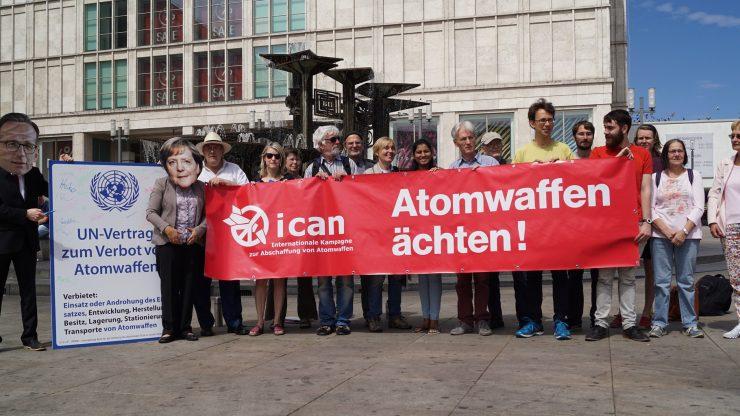 Menschen protestieren mit Bannern auf dem Alexanderplatz