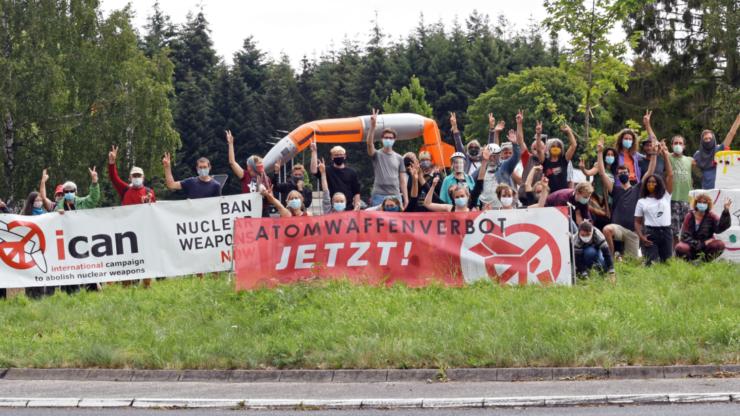 Menschen protestieren auf einem Verkehrskreisel mit Bannern und einer Atomwaffenatrappe